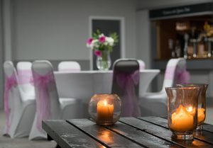 room decorated with white tables, pink chair sashes and flower displays for an evening wedding reception
