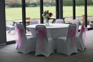 room decorated with white tables, pink chair sashes and flower displays for wedding party
