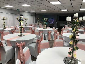 room decorated with white tables, pink chair sashes and gothic flower displays for a wedding party